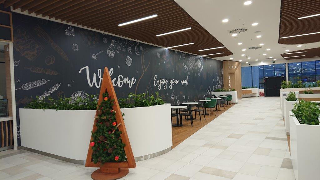 Stoly se židlemi a vánočním stromkem v obchodním centru Olympia, Teplice